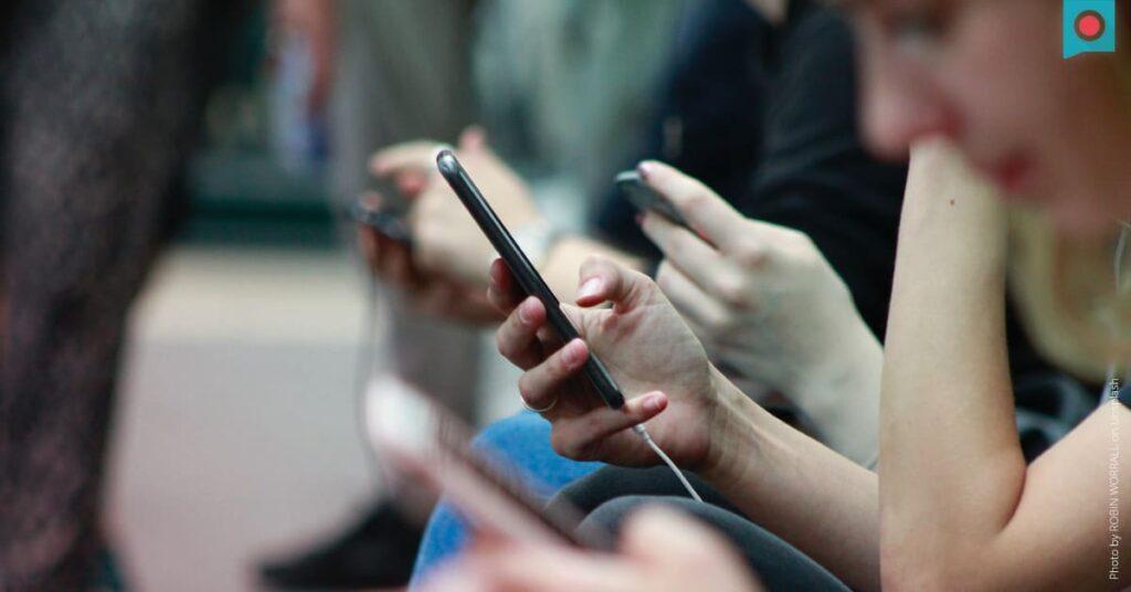 Gruppe Jugendlicher mit Smartphones in den Haenden