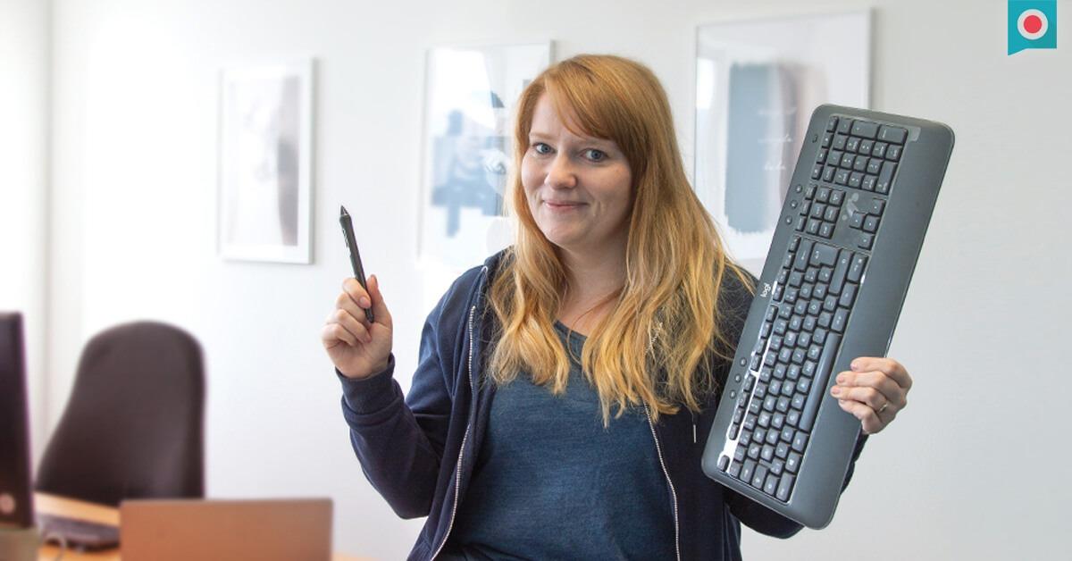 Digital Designerin mit Tastatur und Stift in der Hand