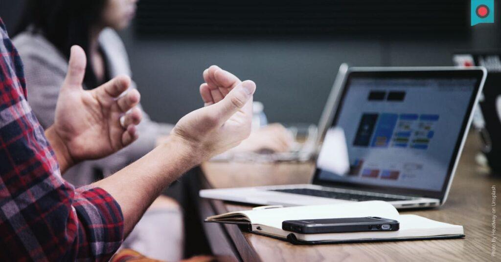 Mit Hängen gestikulierender Mitarbeiter am Arbeitsplatz