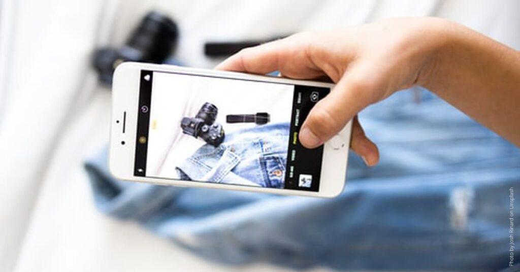 Smartphone fotografiert Jeans und Kamera