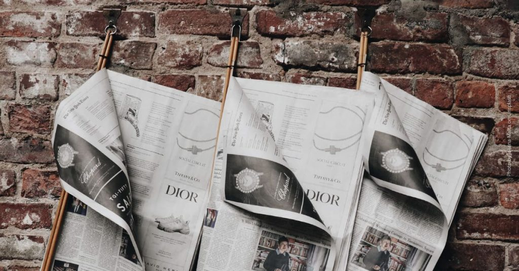 Aufgeschlagene Zeitungen vor Backsteinmauer