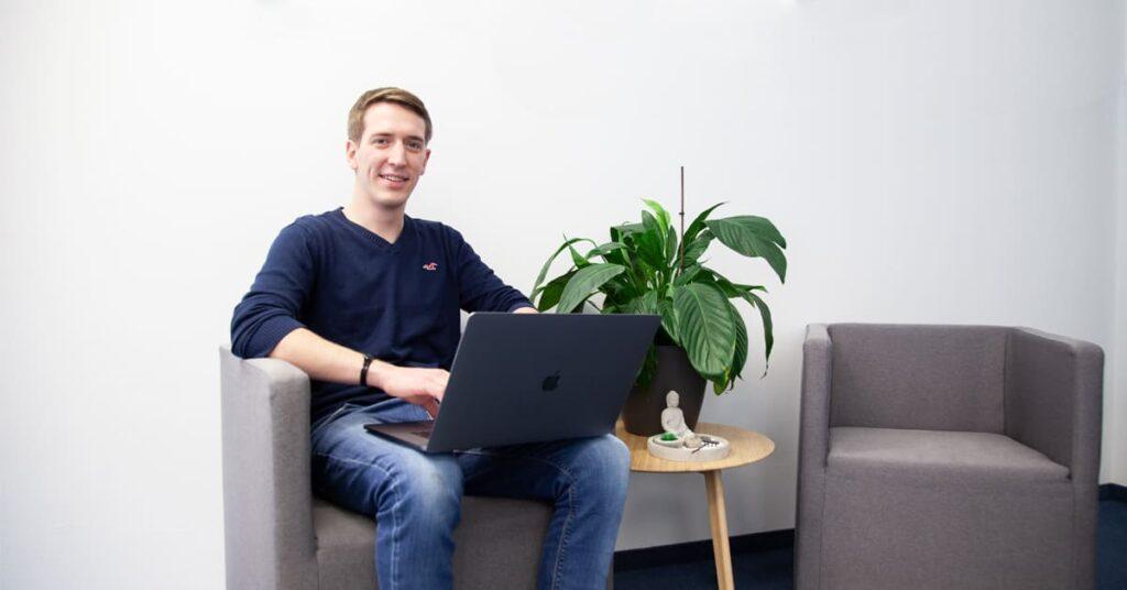 Digital Designer auf Sessel mit Laptop