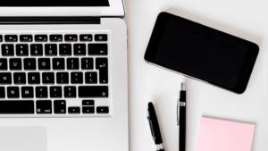 Arbeitsplatz Ausschnitt mit Smartphone, Laptop, Stiften