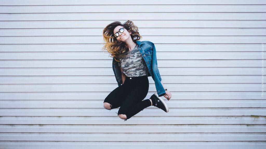 junge Frau im Sprung vor grauer Wand