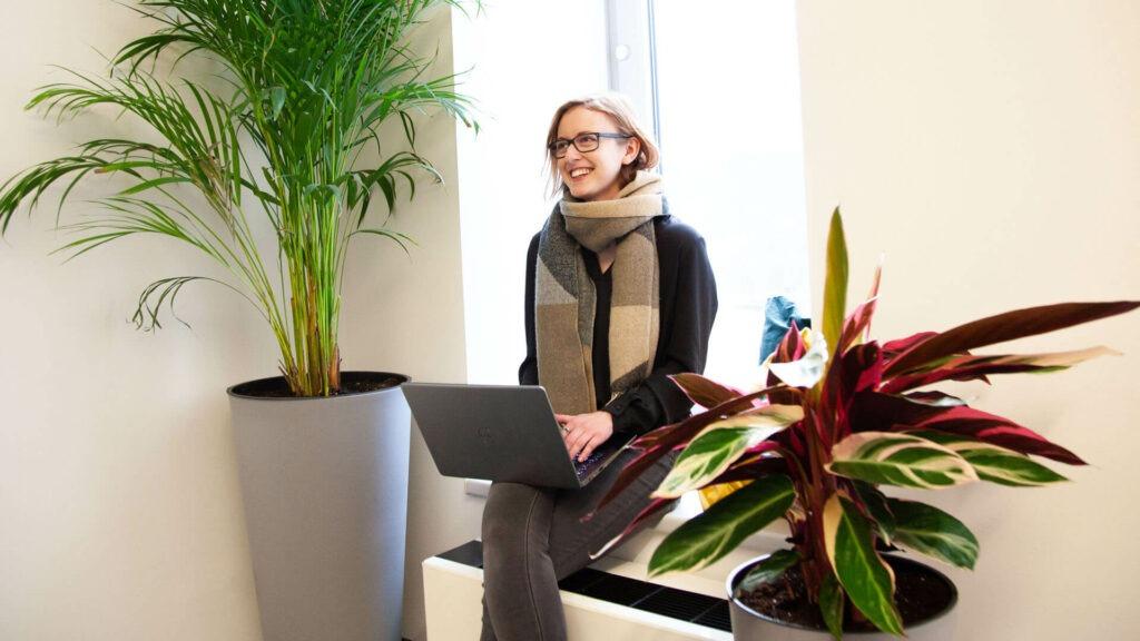 Mitarbeiterin beim Follow-Up Interview am Bürofenster