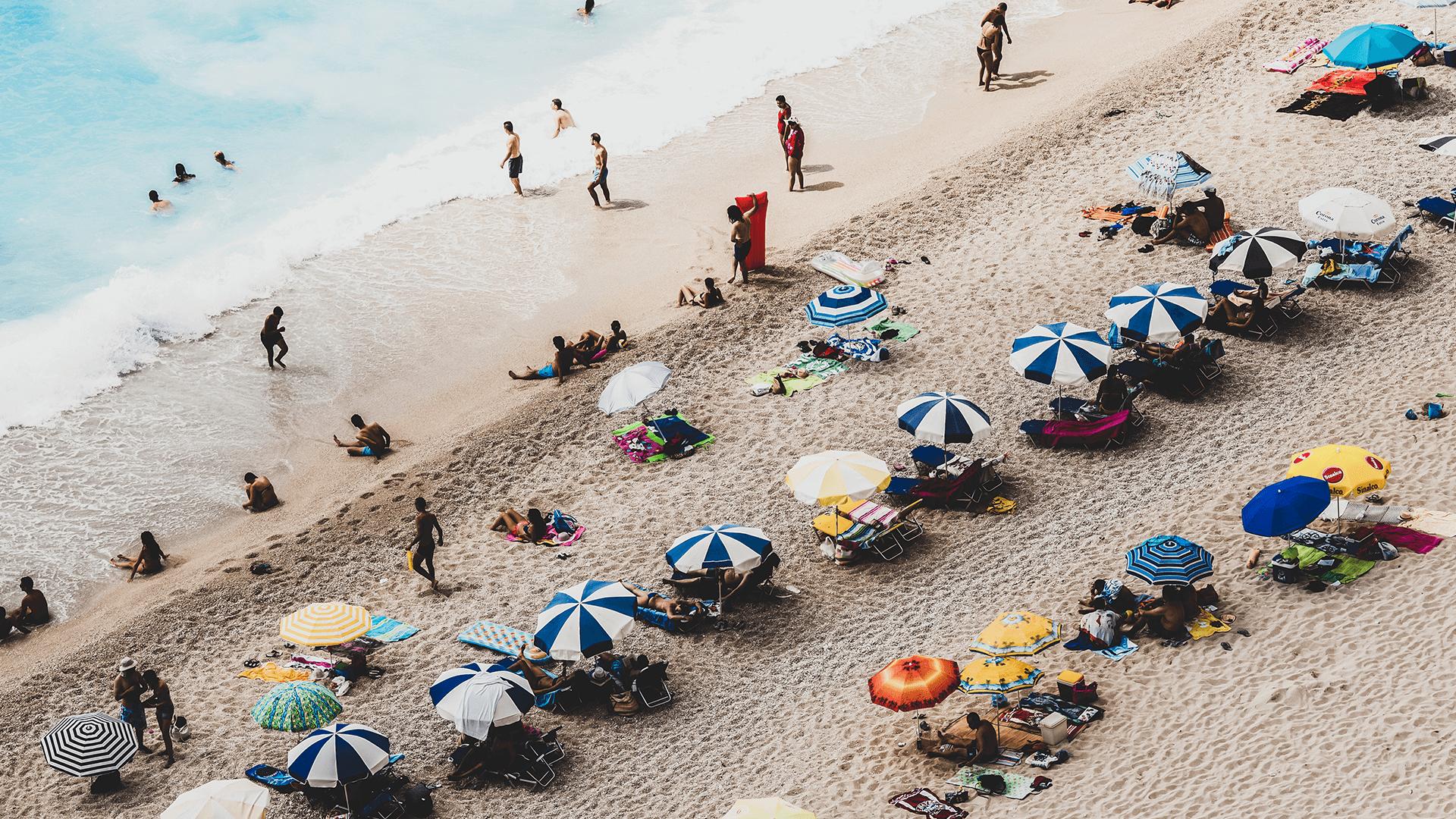 Touristen am Strand mit Meer