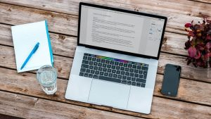 MacBook mit Arbeitsutensilien