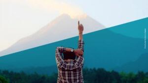 Person steht vor einem Berg und zeigt nach oben