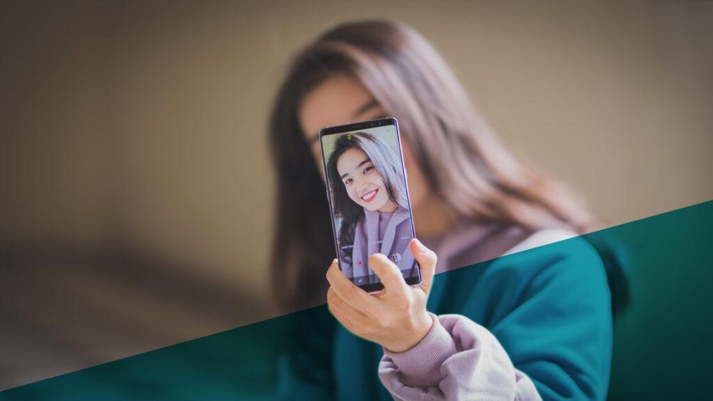 Junge Frau mit braunen Haaren macht Selfie