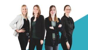 Vier Frauen in Business-Kleidung vor einem weiß-blauen Hintergrund