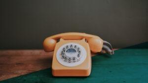 Altes Telefon mit Wählscheibe auf Holztisch
