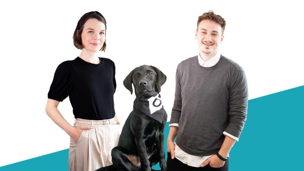 Eine weibliche und eine männliche Person sowie ein schwarzer Hund posieren vor einem blau-weißen Hintergrund