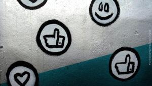 Buttons mit Daumen hoch, Smiley und Herz auf einer silbernen Wand