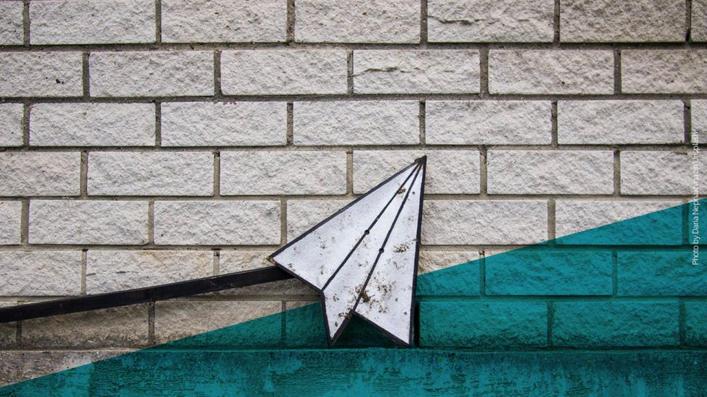 Papierflugzeug aus Eisen vor einer Steinmauer