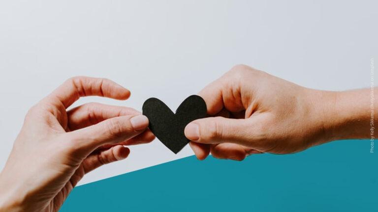 Zwei Hände, die ein kleines, schwarzes Herz überreichen