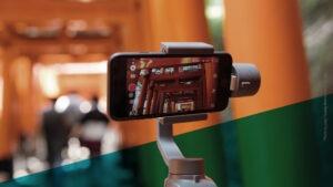 Smartphone auf Stativ mit Blick nach oben filmt Gebäude aus Säulen