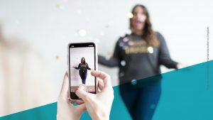 Frau unscharf im Hintergrund wirft Konfetti und wird dabei gefilmt