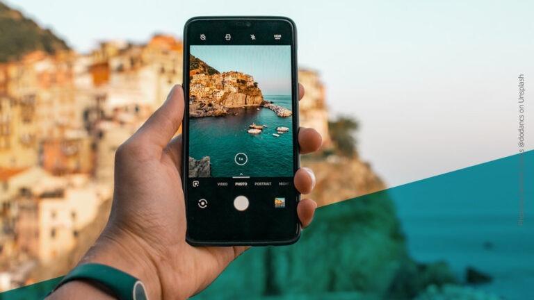 Smartphone in einer Hand macht Foto von einer Landschaft