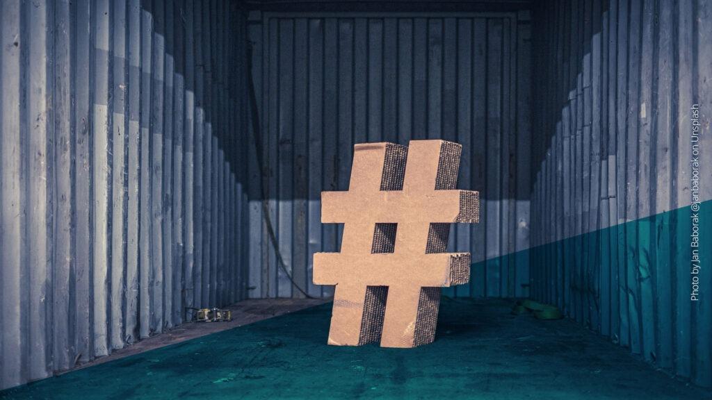 Großes Hashtag-Symbol aus Holz vor einer Wellblech-Wand platziert