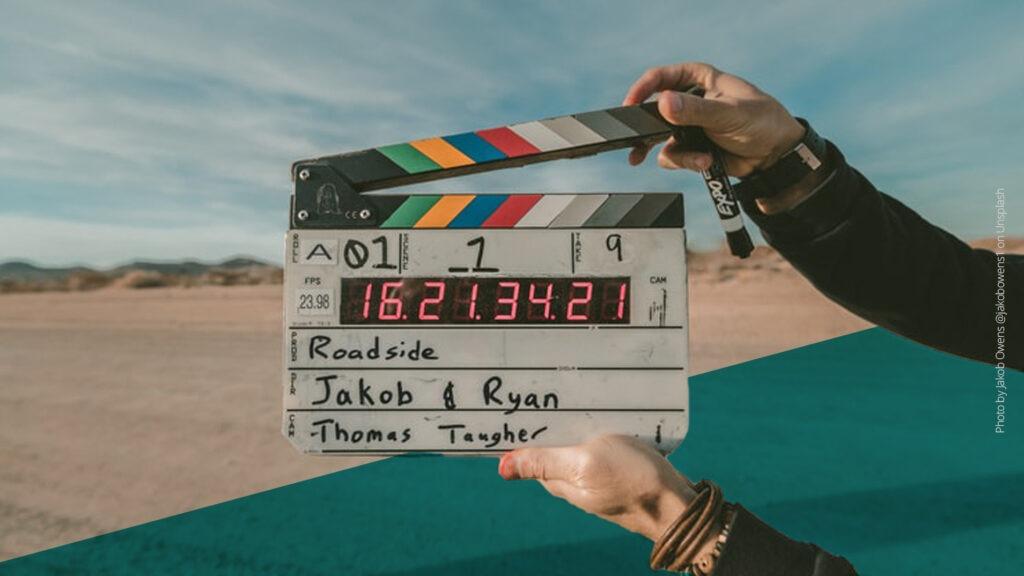 Filmklappe wird vor die Kamera gehalten, im Hintergrund ist eine Wüstenlandschaft