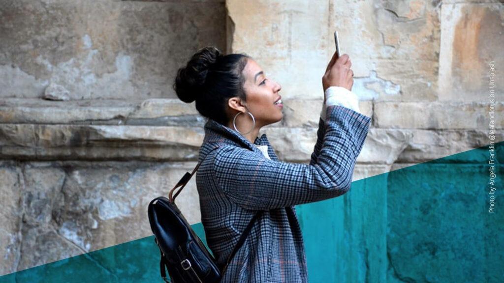 Junge Frau hält ihr Handy nach oben und schaut interessiert darauf