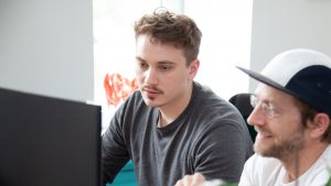 Zwei Männer sitzen vor einem PC und arbeiten