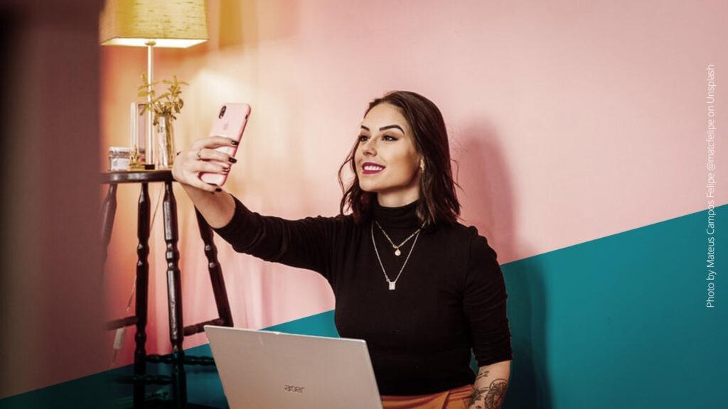 Junge Frau mit dunklen Haaren und Laptop auf dem Schoß macht ein Selfie vor einer pinken Wand