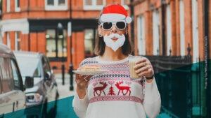 Frau mit Sonnenbrille, Weihnachtsmannmütze und weißem Kostüm-Bart, die einen Milchkaffe und ein Stück Kuchen in der Hand hält, steht auf der Straße