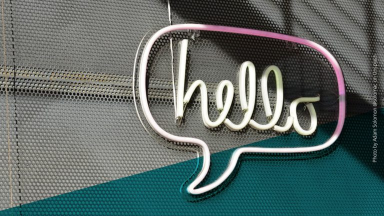 """Sprechblase mit Schriftzug """"hello"""" aus Leuchtröhren an einer Wand"""