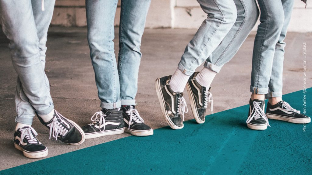 Vier Beine nebeneinander, alle tragen helle Jeans und schwarzweiße Schuhe